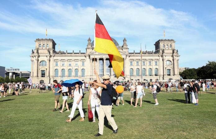 demonstrator holds a German flag