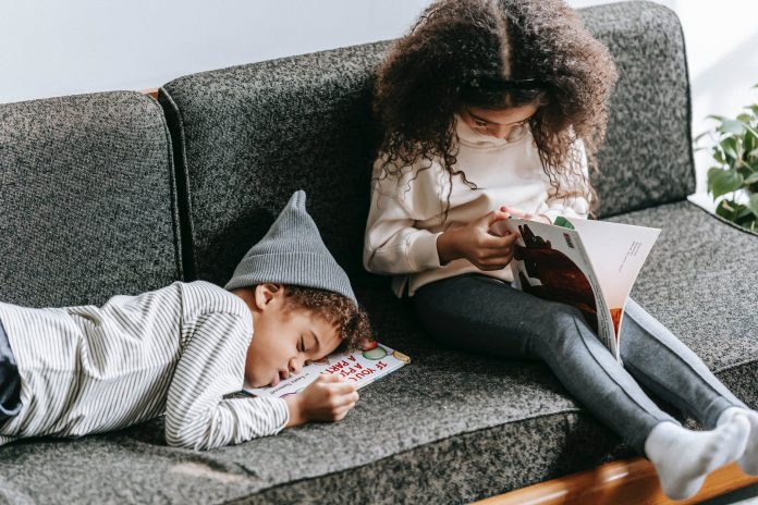 black little boy napping on couch near sister reading book