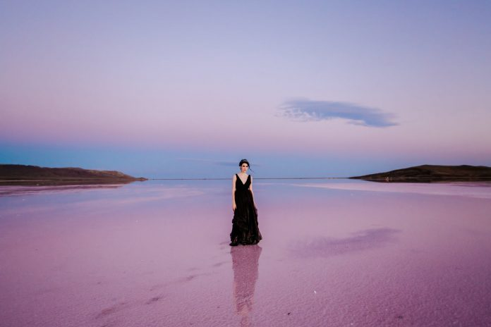 fashionable young lady standing on pink sandy shore under sundown sky