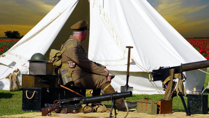 man sitting on chair near white tent