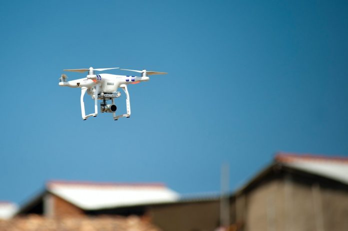 selective focus photograph of white quadcopter drone during blue hour