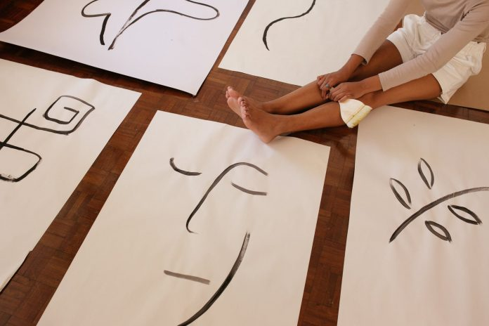 crop woman and abstract illustrations on floor