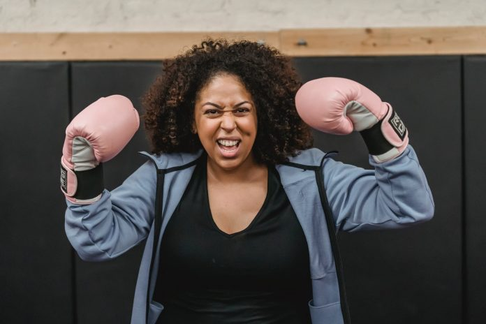 excited young black sportswoman showing biceps after boxing training