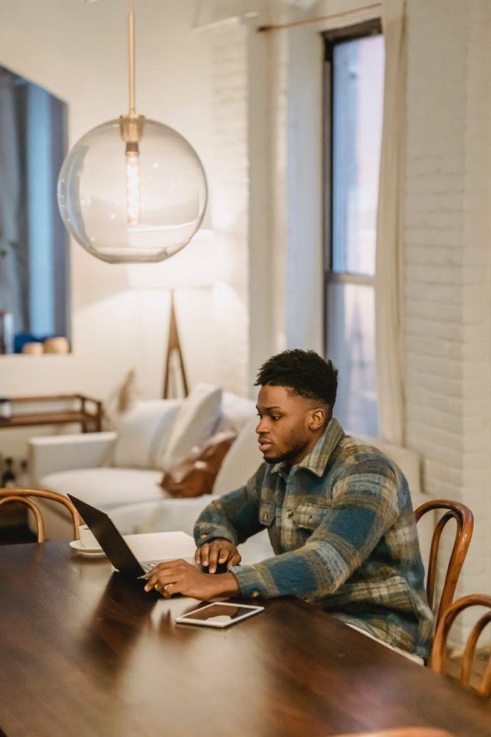 serious black man working on laptop at home