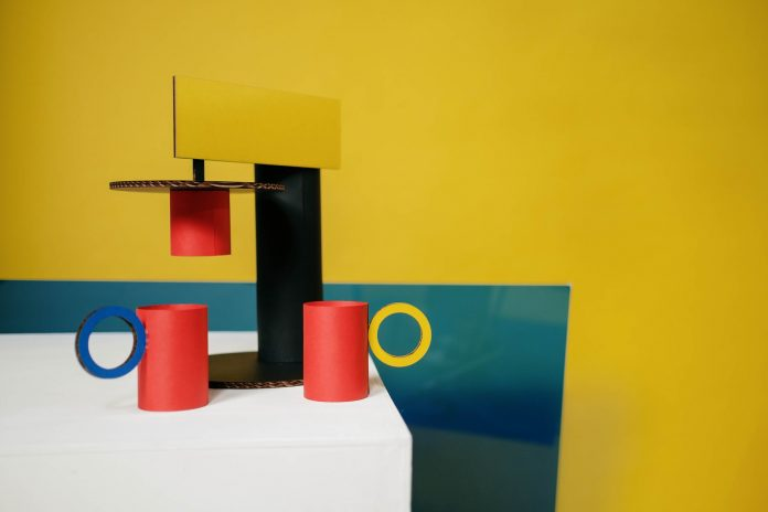 creative composition of colorful cardboard cups and coffeemaker arranged on table