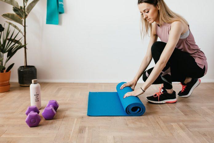 crop fit sportswoman unfolding fitness mat on floor