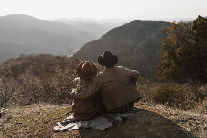 unrecognizable couple hugging and sitting on picturesque hilly terrain