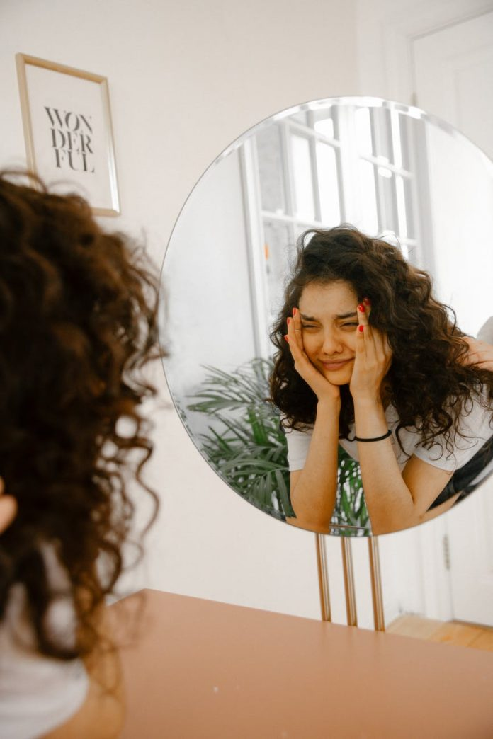 upset woman looking in mirror