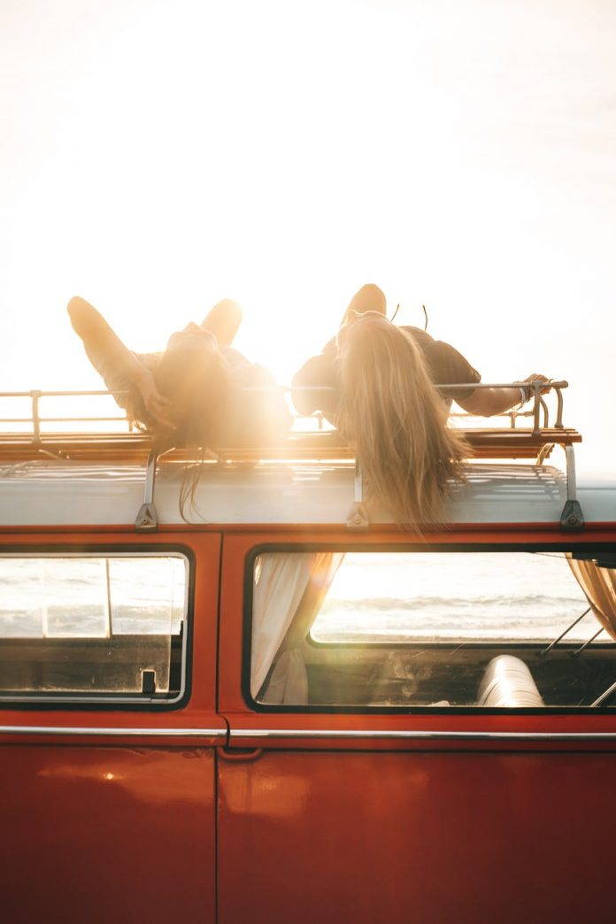 friends lying on trunk of retro car on sunny day
