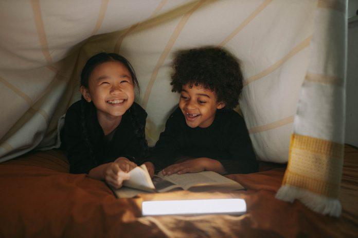 girl and boy having fun while reading a book