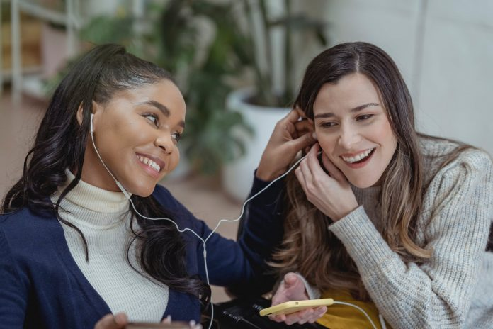 delighted young multiethnic female friends smiling and listening to music in earphones