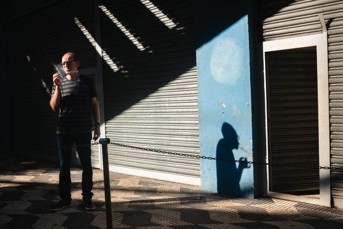photo of man smoking while standing near roller shutter