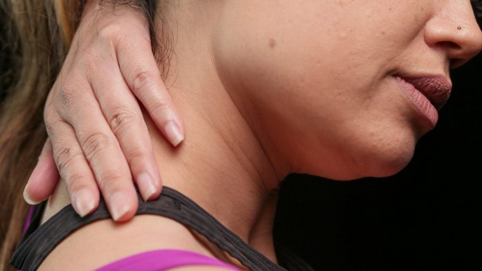 close up photo of a woman having a neck pain