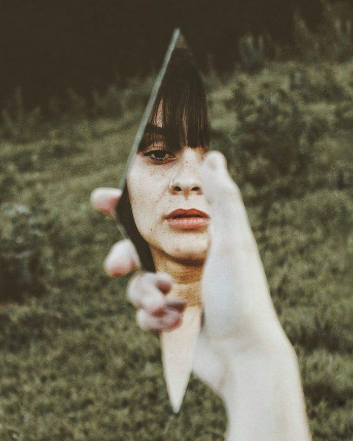 woman holding broken mirror