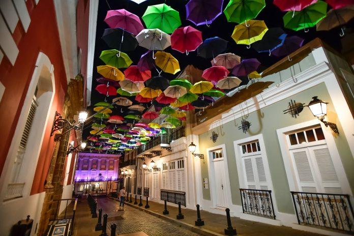 assorted coloured umbrellas hanging near buildings