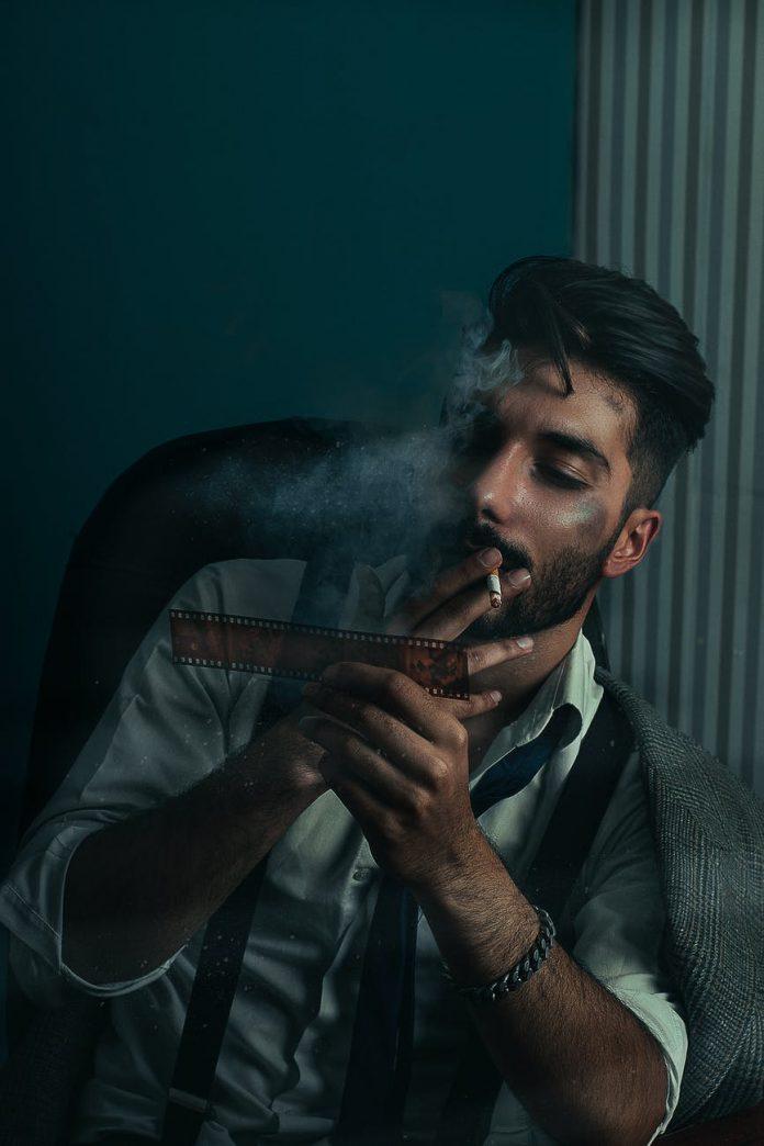 serious ethnic man smoking while examining filmstrip